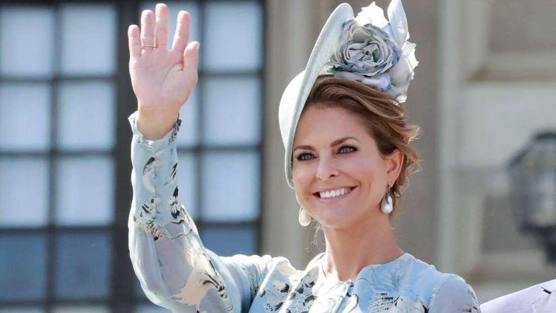Prinzessin Madeleine trägt einen auffälligen Hut und winkt mit der rechten Hand (Symbolbild).