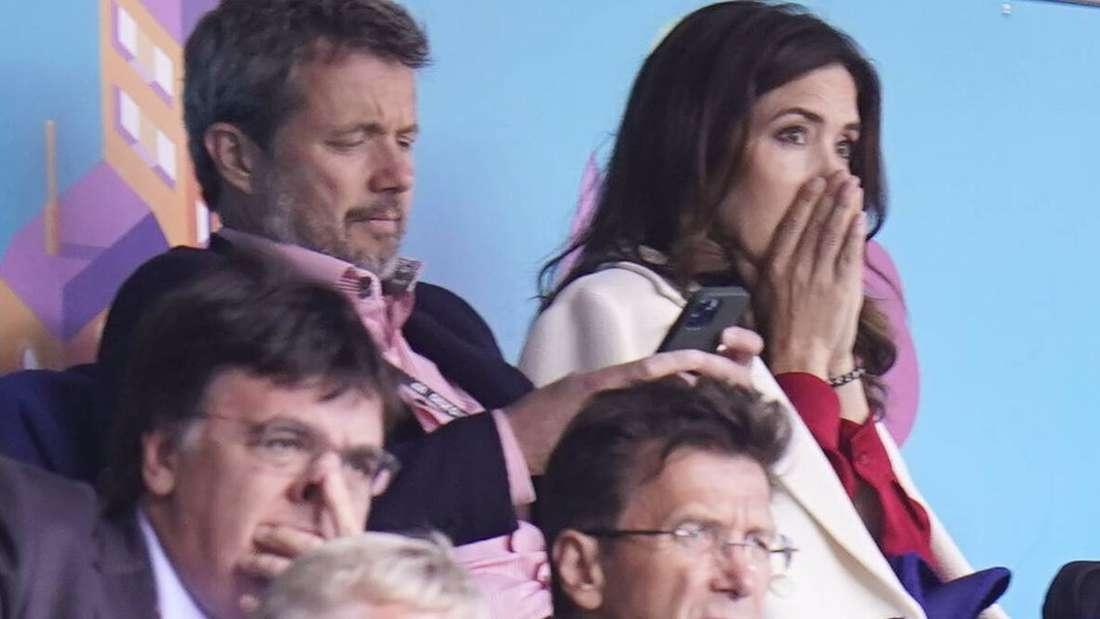 Kronprinz Frederik und Kronprinzessin sitzen hinter mehreren Männern, sie hält sich die Hände vor ihr Gesicht.