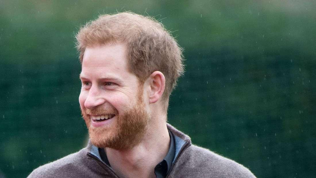 Prinz Harry blickt zur Seite und lächelt.