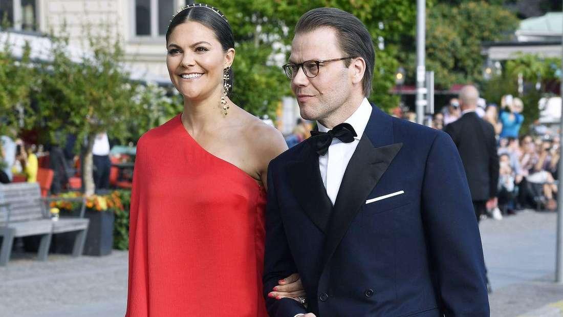 Kronprinzessin Victoria trägt ein rotes Kleid und läuft lächelnd neben ihrem Ehemann Prinz Daniel her.