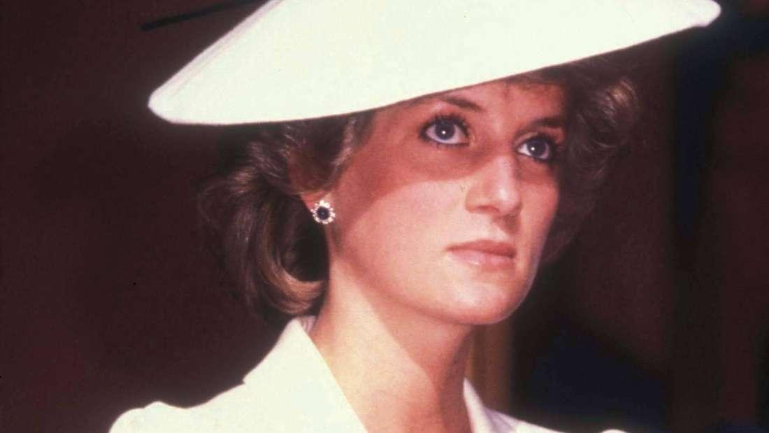 Prinzessin Diana trägt einen Hut und schaut ernst.