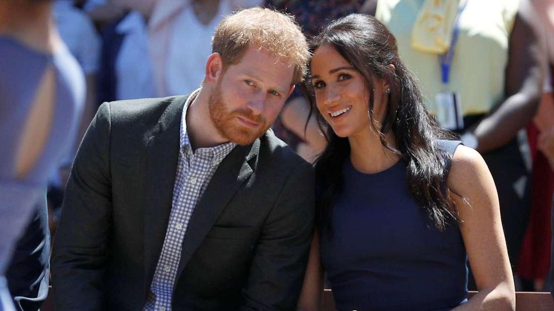 Prinz Harry und Herzogin Meghan sitzen nebeneinander und stecken die Köpfe zusammen.