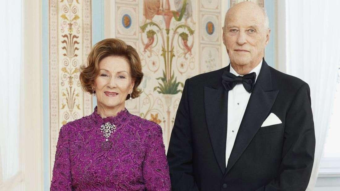 Königin Sonja und König Harald von Norwegen stehen festlich gekleidet nebeneinander.