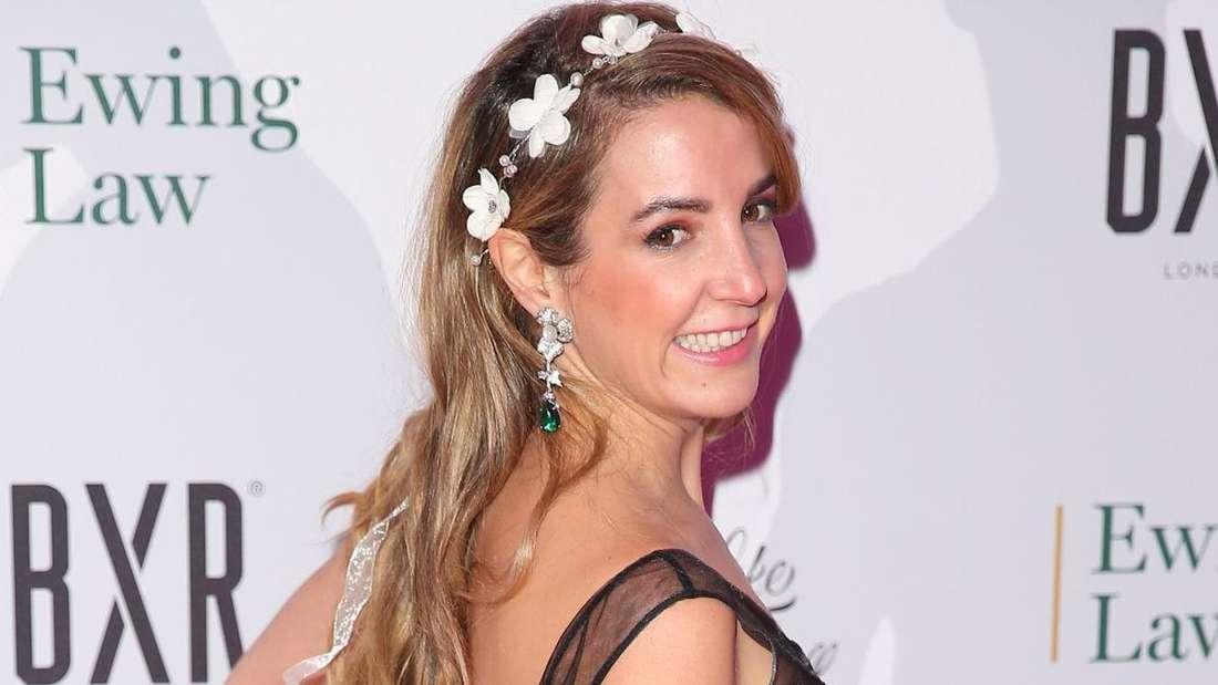 Tessy Antony de Nassau trägt ein schwarzes Abendkleid und lächelt über ihre Schulter in die Kamera.