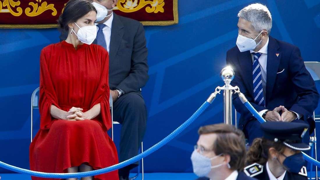 Königin Letizia sitzt in einem roten Kleid hinter einer Absperrung auf einem Stuhl und unterhält sich mit einem Mann, der neben ihr sitzt.