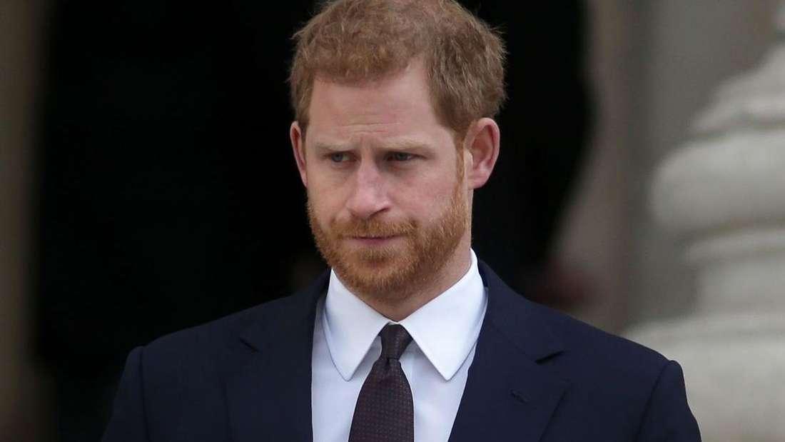 Prinz Harry trägt einen dunklen Anzug und schaut ernst (Symbolbild).