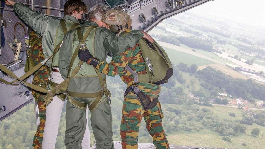 Prinz Gabriel und König Philippe stehen mit zwei Fallschirmjägern auf der Rampe in einem Flugzeug.