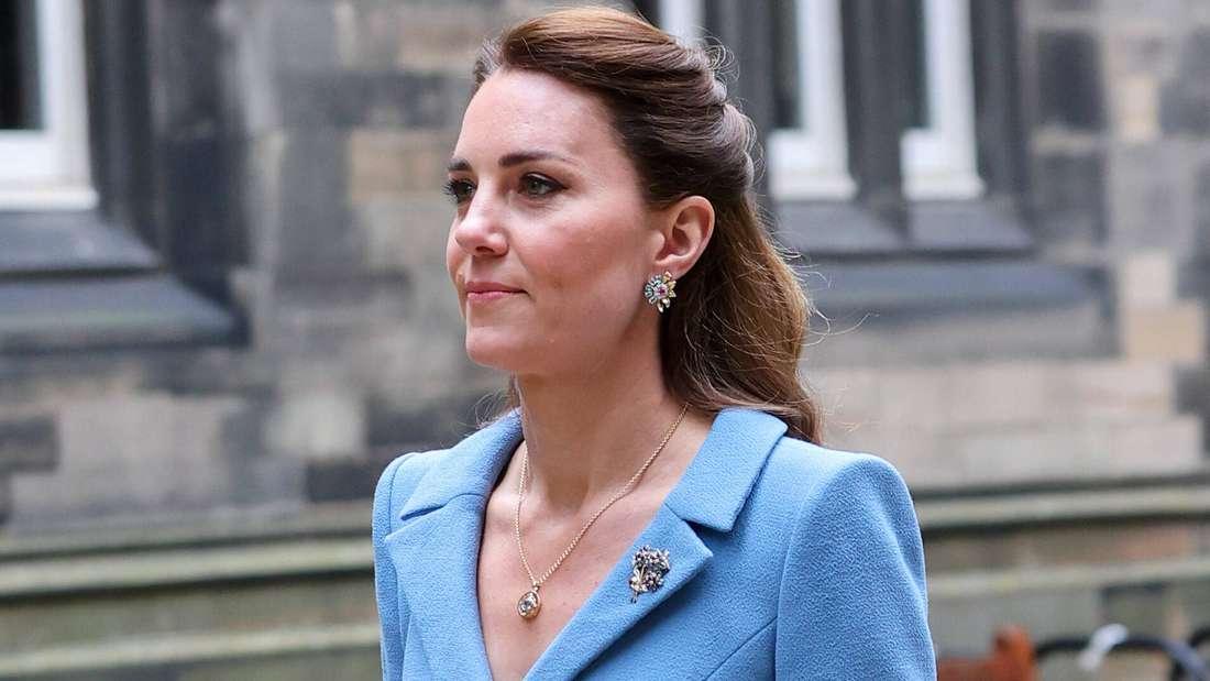 Herzogin Kate trägt einen hellblauen Mantel und blickt ernst geradeaus.