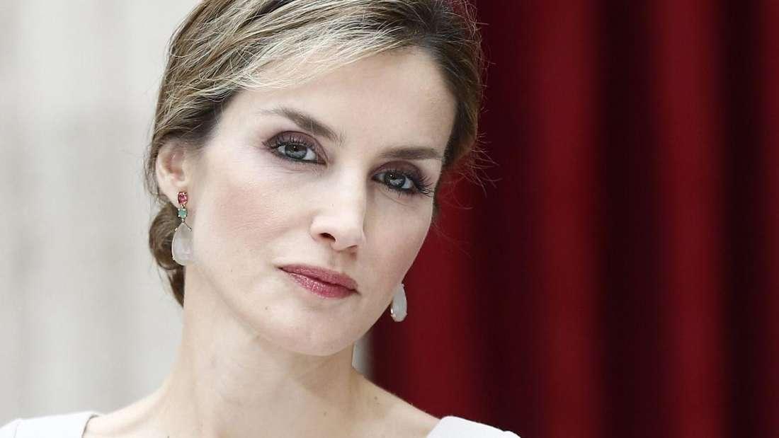 Königin Letizia steht vor einem roten Vorhang und schaut ernst.
