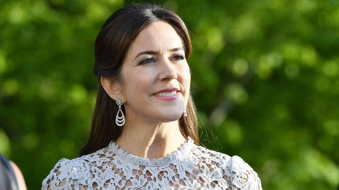 Kronprinzessin Mary trägt ein helles Kleid aus Spitze und lächelt.