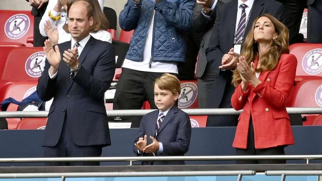 Prinz William steht neben seinem Sohn George und seiner Ehefrau Kate auf einer Tribüne, alle drei klatschen.