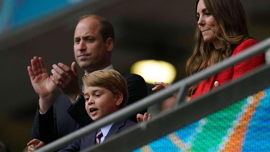 Prinz William steht neben seinem Sohn George und seiner Ehefrau Kate auf einer Tribüne und klatscht.