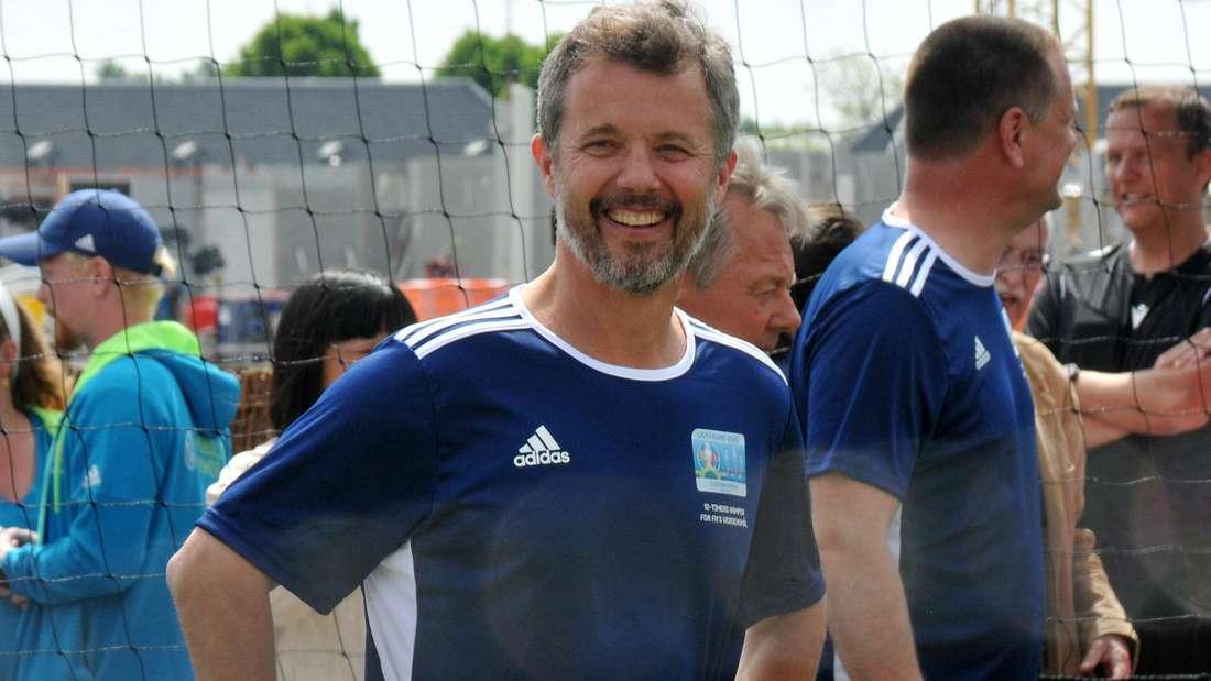 Kronprinz Frederik trägt ein blaues T-Shirt und lächelt (Symbolbild).