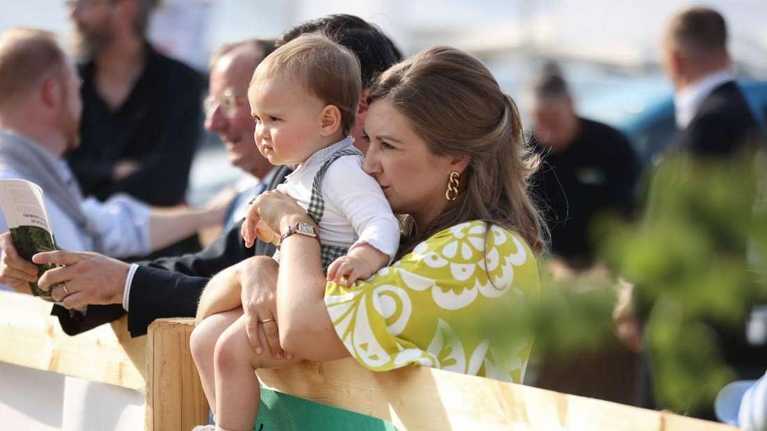 Erbgroßherzogin Stéphanie von Luxemburg hält ihren Sohn Charles, der auf einem Zaun sitzt, im Arm.