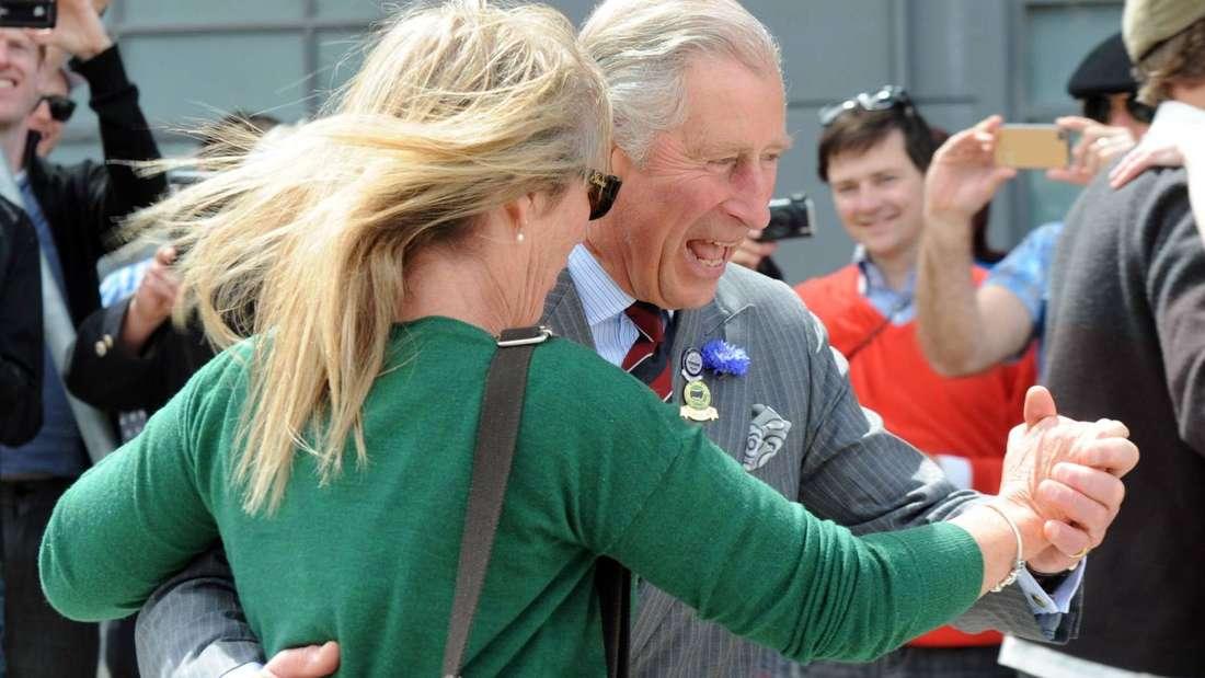 Prinz Charles tanzt mit einer blonden Frau und lacht (Symbolbild).