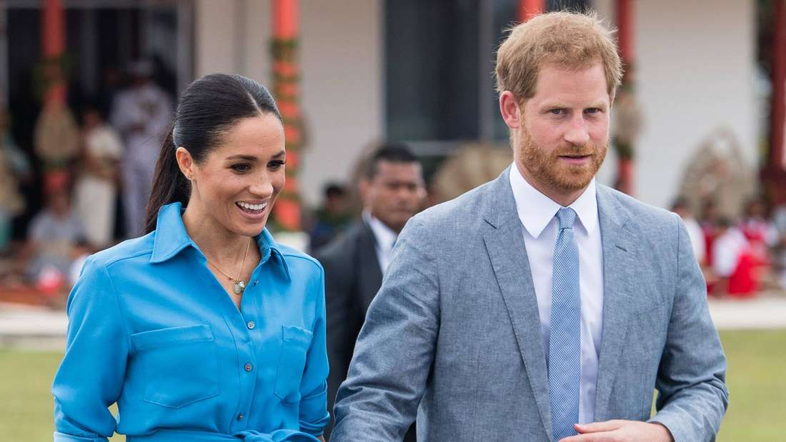 Herzogin Meghan und Prinz Harry stehen nebeneinander und halten Händchen (Symbolbild).