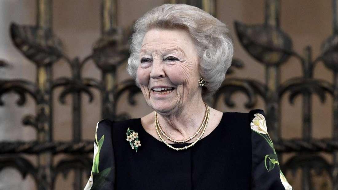 Prinzessin Beatrix trägt ein dunkles Oberteil mit hellen Blüten und lächelt.