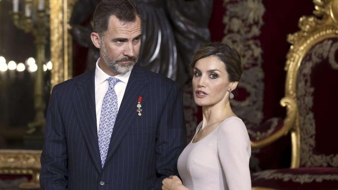 König Felipe und Königin Letizia stehen nebeneinander, beide schauen ernst.