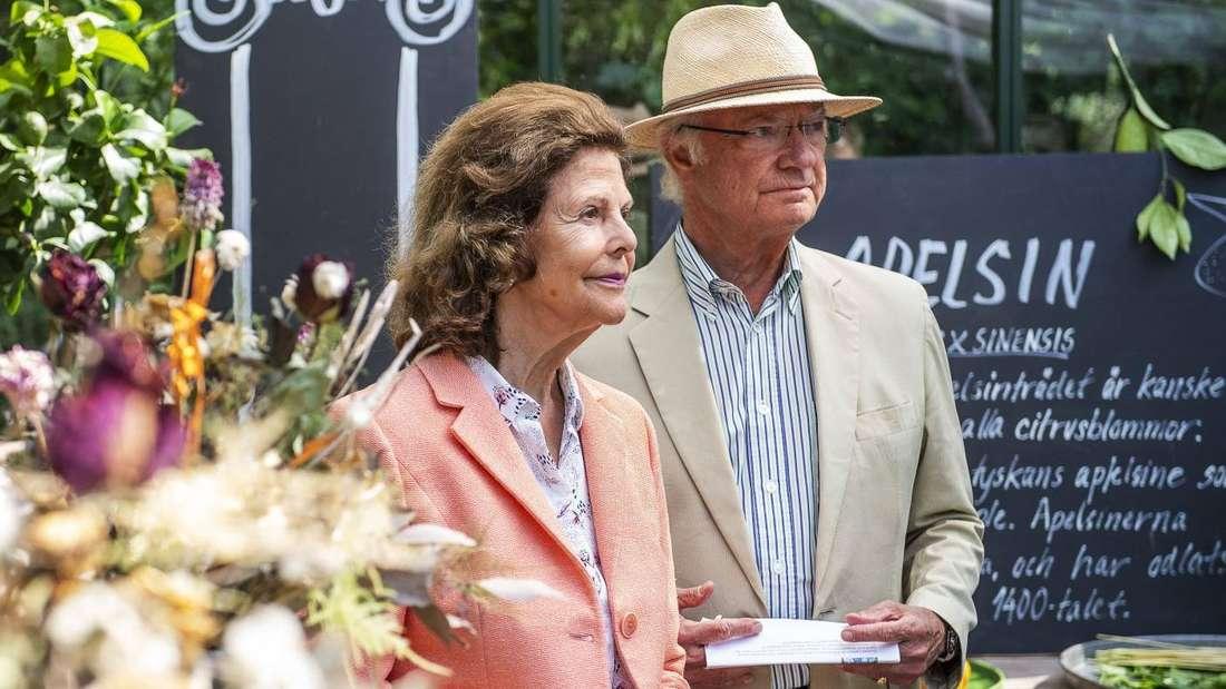 Königin Silvia und König Carl Gustaf stehen nebeneinander, er trägt einen Strohhut und hält ein Papier in der Hand.