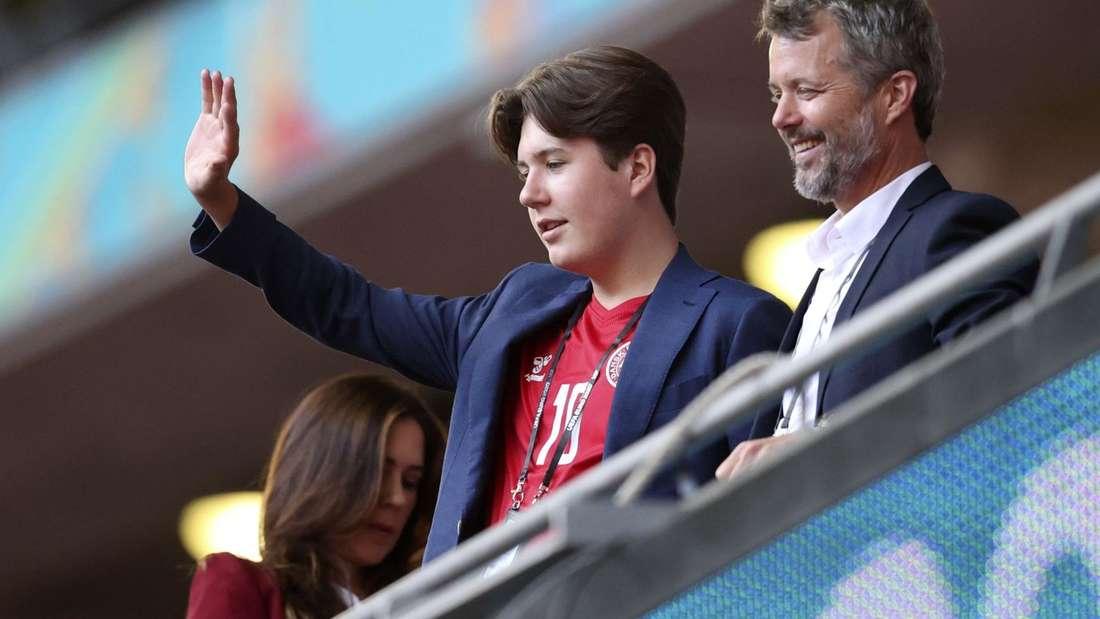 Prinz Christian steht winkend neben seinem Vater Kronprinz Frederik, im Hintergrund ist Kronprinzessin Mary zu sehen.