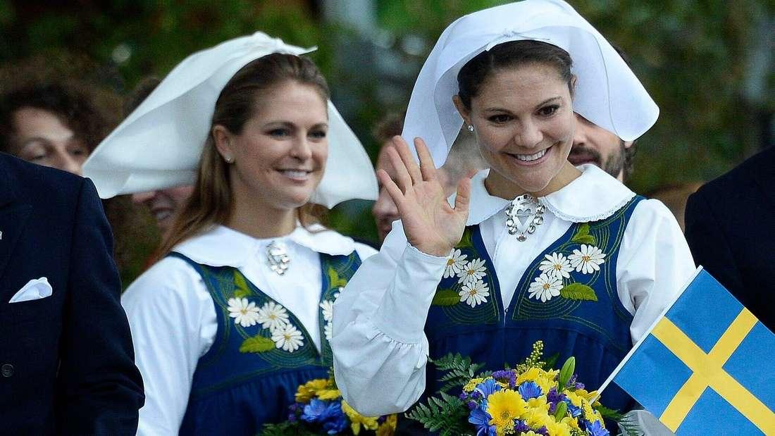 Kronprinzessin Victoria steht vor Prinzessin Madeleine und winkt, beide tragen Tracht (Symbolbild).