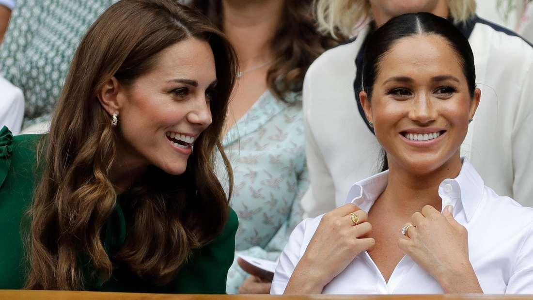 Herzogin Kate und Herzogin Meghan sitzen fröhlich lächelnd nebeneinander (Symbolbild).