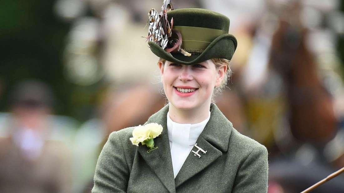Lady Louise trägt einen auffälligen Hut und sitzt auf einer Kutsche.
