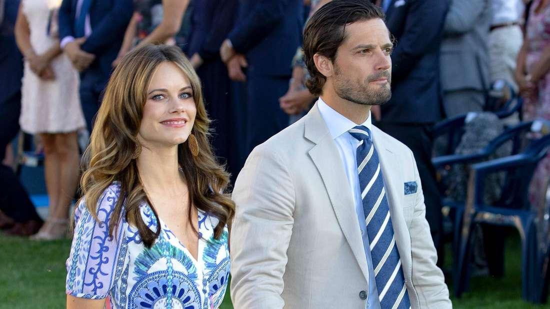 Prinzessin Sofia hält einen Blumenstrauß in der rechten Hand und läuft Hand in Hand mit ihrem Ehemann Carl Philip über einen Rasen (Symbolbild).
