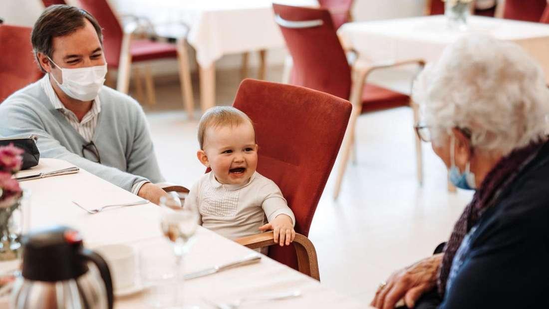 Prinz Charles von Luxemburg sitzt neben seinem Vater Erbgroßherzog Guillaume und lächelt.
