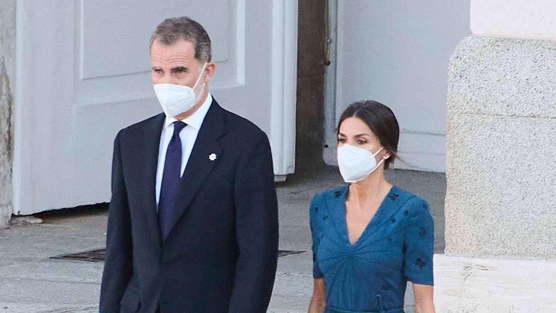 König Felipe VI. und Königin Letizia von Spanien laufen nebeneinander und tragen Schutzmasken.