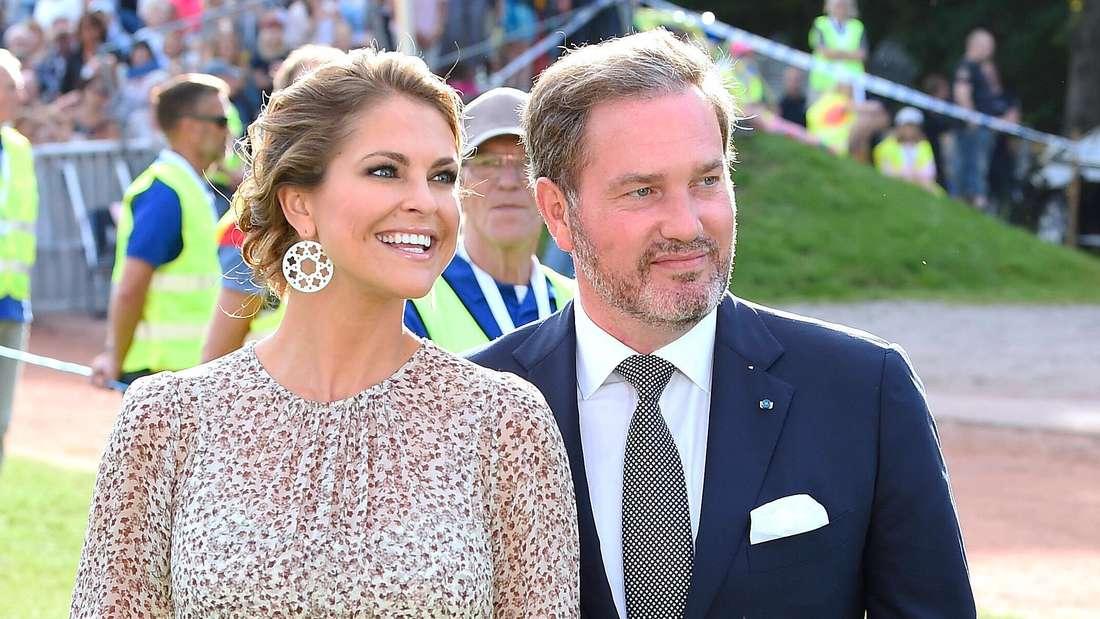 Prinzessin Madeleine von Schweden und ihr Ehemann Chris O'Neill stehen nebeneinander und lächeln.