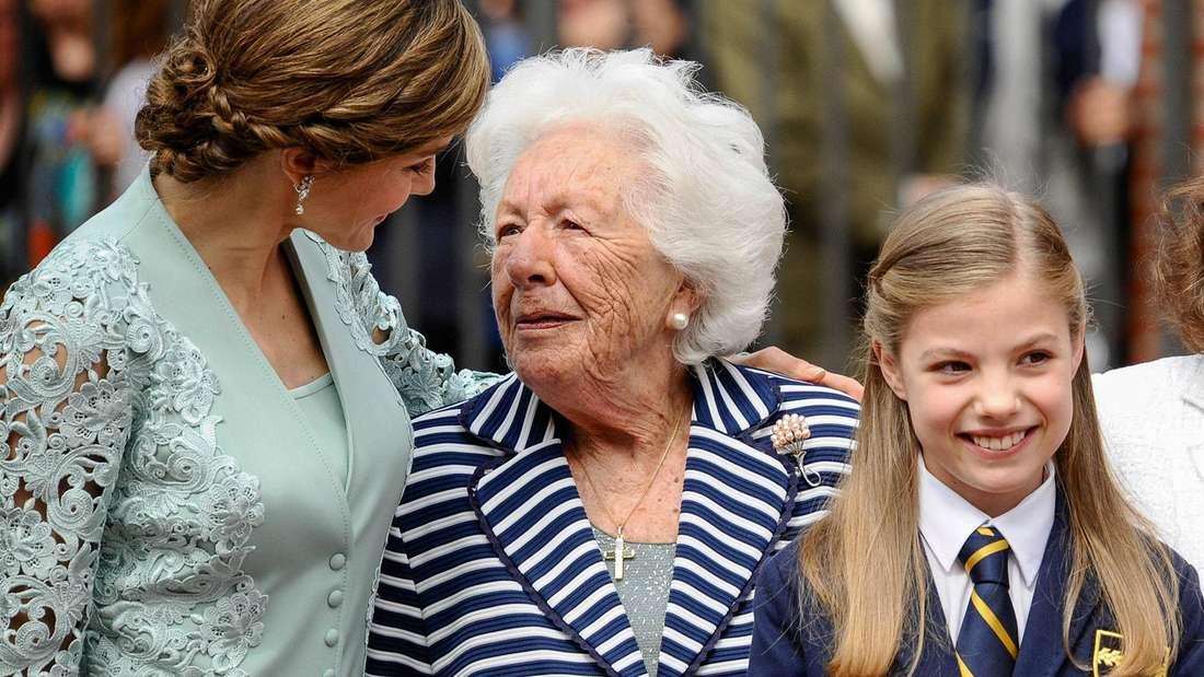 Königin Letizia hat den Arm um ihre Großmutter gelegt, vor ihnen steht lächelnd Infantin Sofía.