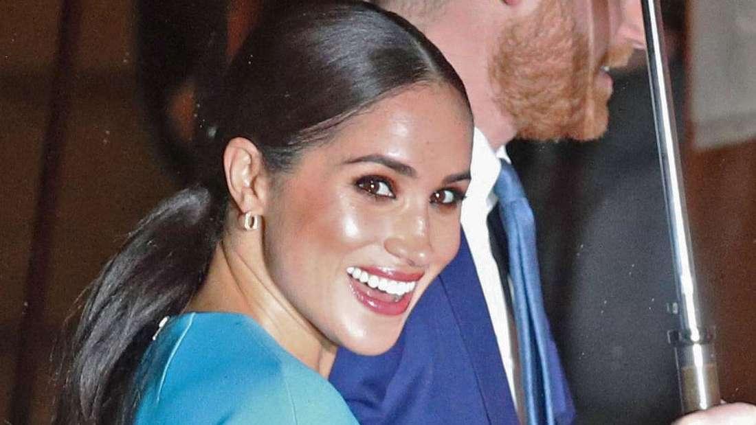 Meghan schaut in die Kamera, Prinz Harry trägt den Regenschirm auf dem Weg zur Verleihung der Endeavour Fund Awards in London ein (Symbolbild).
