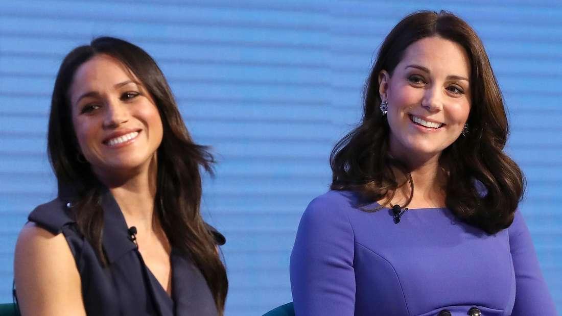 Herzogin Kate und Herzogin Meghan sitzen nebeneinander und lachen (Symbolbild).