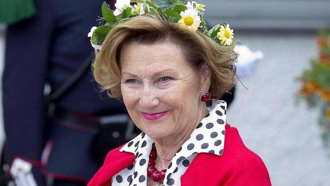 Königin Sonja trägt einen Blumenkranz im Haar und lächelt (Symbolbild).