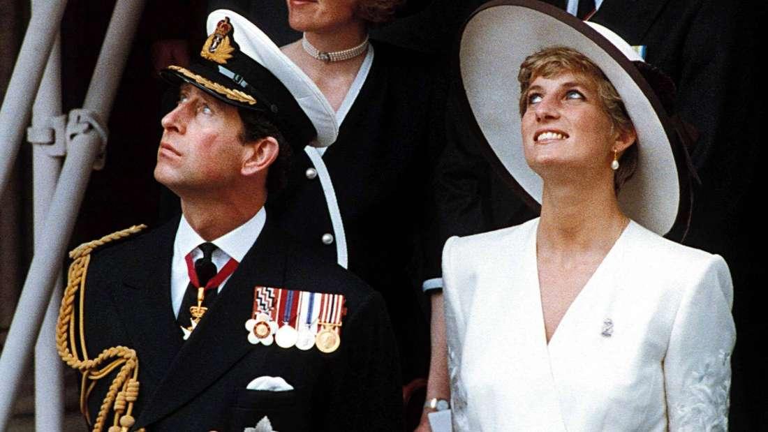 Prinz Charles und Prinzessin Diana stehen nebeneinander und schauen nach oben.