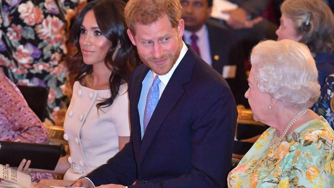 Queen Elizabeth II. sitzt neben Prinz Harry, der zu ihr blickt, und Herzogin Meghan.