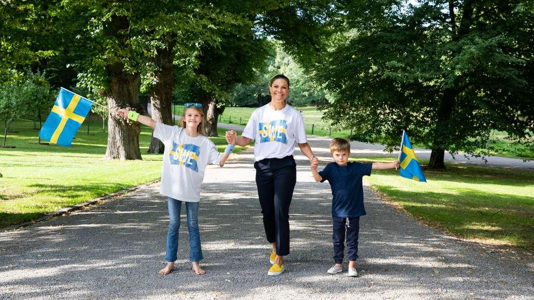Prinzessin Estelle, Kronprinzessin Victoria und Prinz Oscar laufen Hand in Hand einen Weg entlang, die Kinder haben Schweden-Flaggen in der Hand.