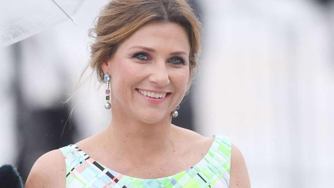 Prinzessin Märtha Louise trägt ein türkisfarbenes Abendkleid und lächelt.