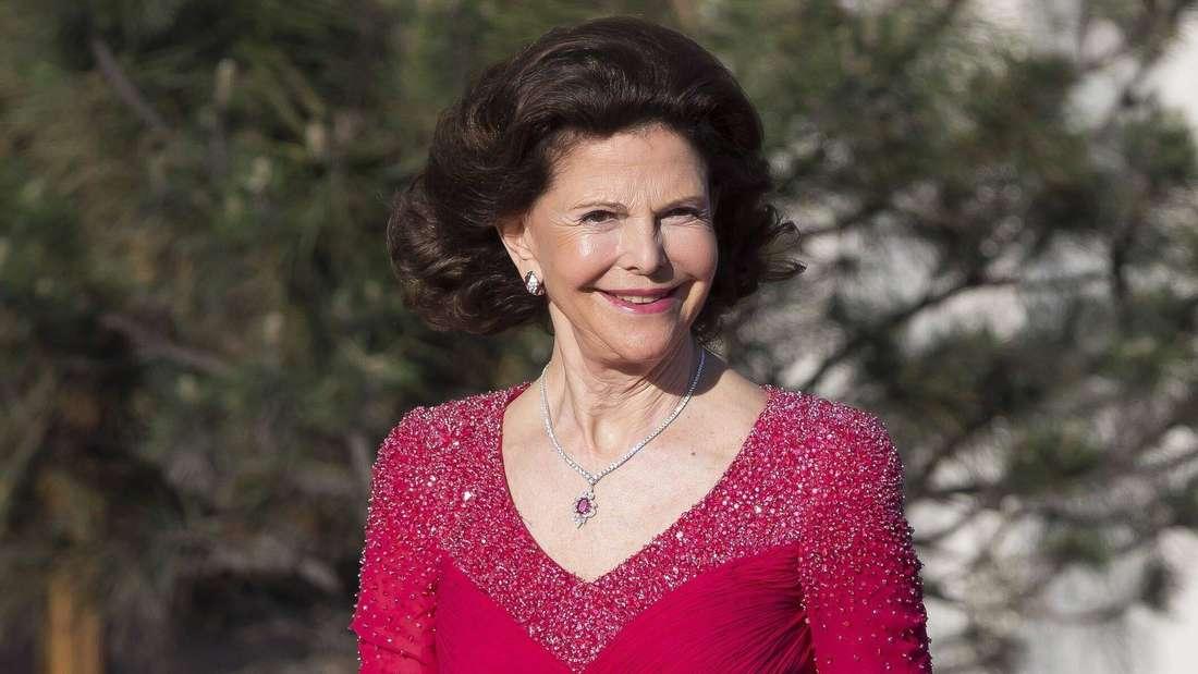 Königin Silvia von Schweden trägt ein rotes Abendkleid und lächelt.