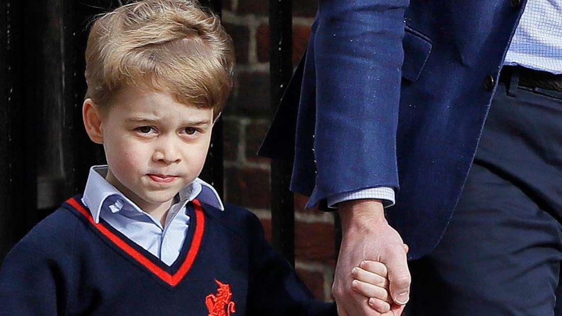 Prinz George hält einen Erwachsenen an der Hand und schaut nachdenklich.