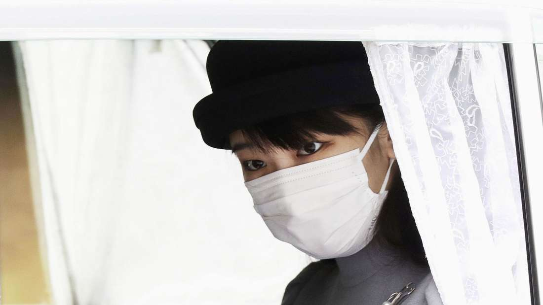 Japans Prinzessin Mako blicket aus dem Limosienenfenster und trägt eine Schutzmaske und Hut