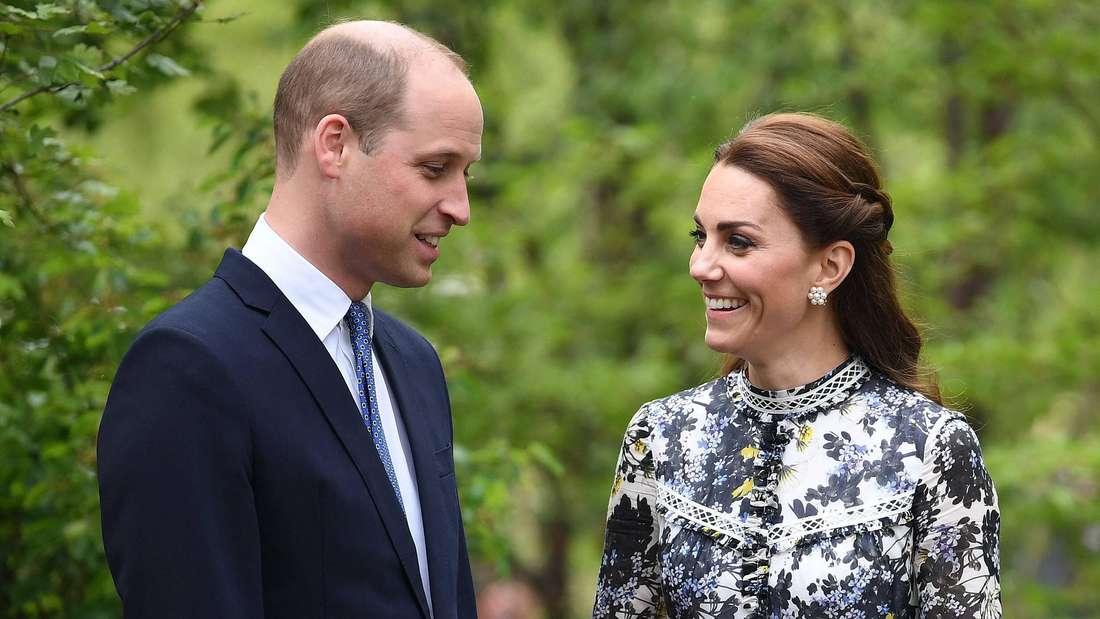 Prinz William und Herzogin Kate stehen nebeneinander und blicken sich an.