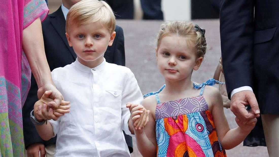 Erbprinz Jacques von Monaco und seine Schwester Gabriella halten sich und jeweils einen Erwachsenen an der Hand.
