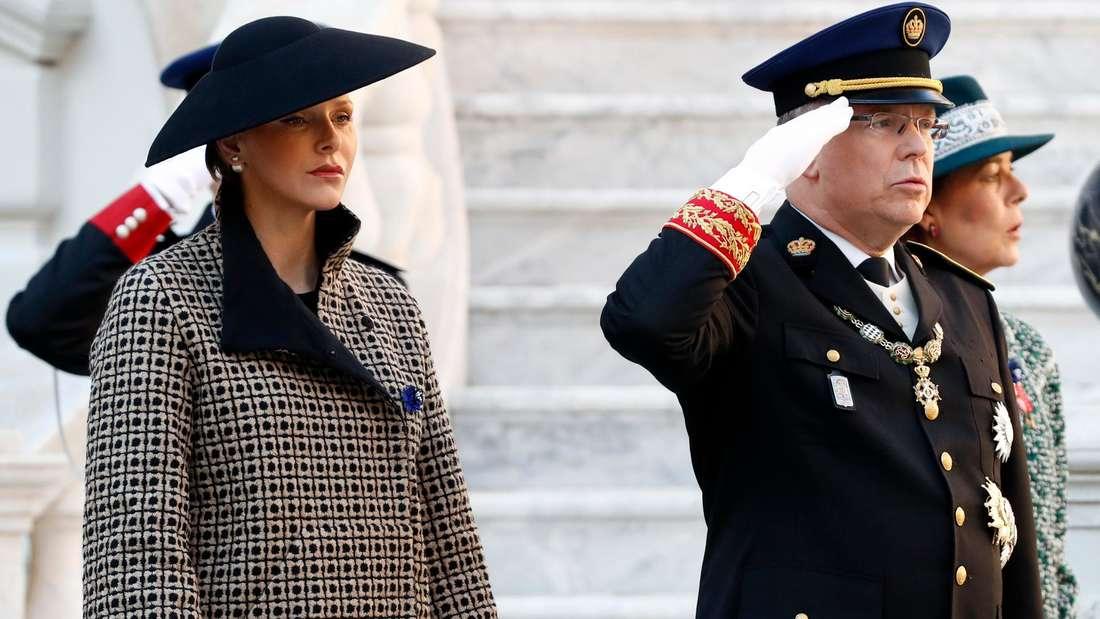 Fürstin Charlène und Fürst Albert stehen nebeneinander, er salutiert.