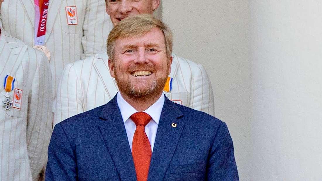 König Willem-Alexander lächelt und steht vor dem Paleis Noordeinde.
