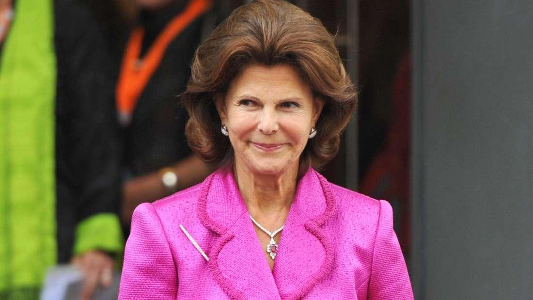 Königin Silvia trägt einen pinkfarbenen Blazer und lächelt.