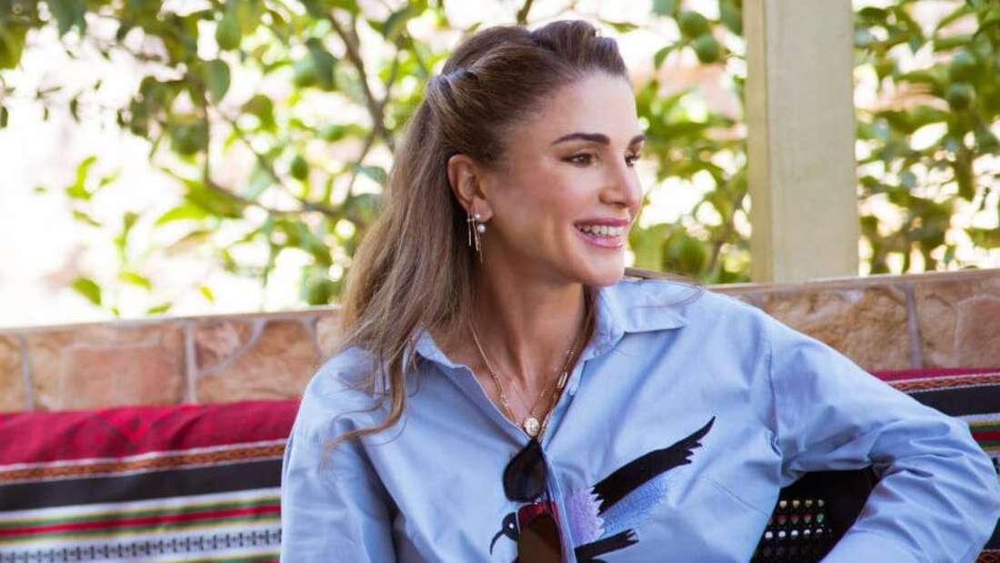 Königin Rania von Jordanien sitzt auf einem Stuhl und blickt lächelnd zur Seite.