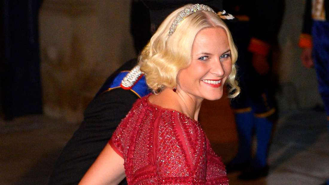 Kronprinzessin Mette-Marit trägt ein rotes Kleid und schaut über ihre rechte Schulter nach hinten.