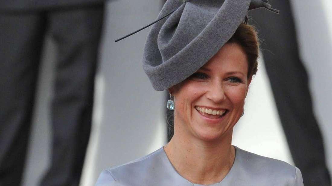 Prinzessin Märtha Louise von Norwegen lächelt und trägt einen grauen Hut (Symbolbild).